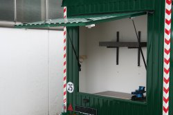 Overhead workshop door with workbench, rotary vise, shelf, and holders for brush cutters